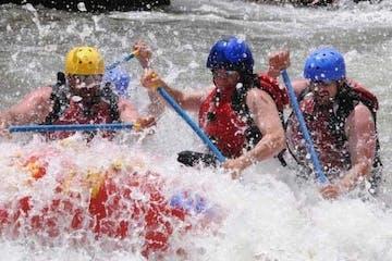 group rafting down splashing rapids