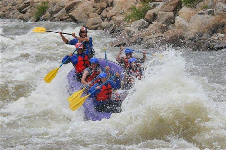 group splashing through rapids on raft