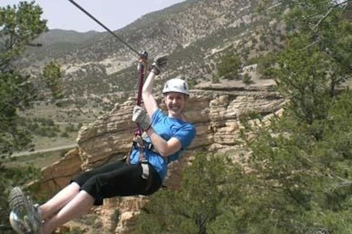 woman smiling going down a zipline in a canyon