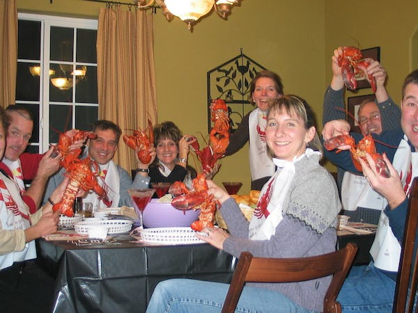 Family sitting around table eating lobster