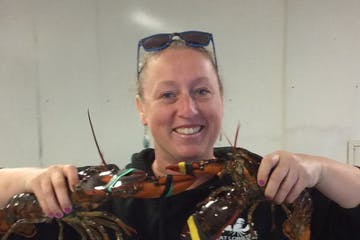 a person holding a lobster