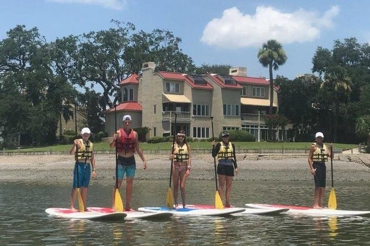 Group on stand up paddle boards near the shore