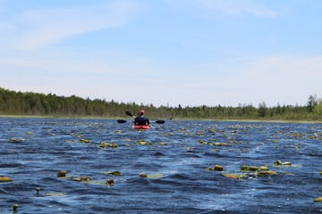 two guests paddle a tandem kayak