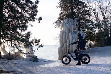 a man riding a motorcycle on the side of a snow covered slope