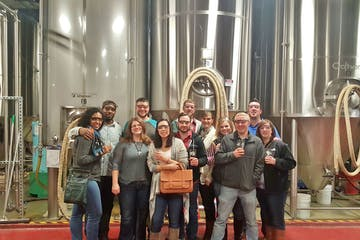 tour group standing in front of brewing barrels