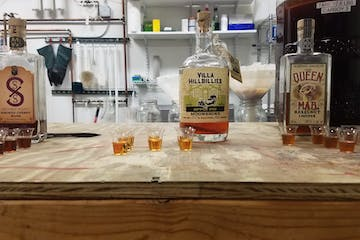 bottles of whiskey with shot glasses on counter
