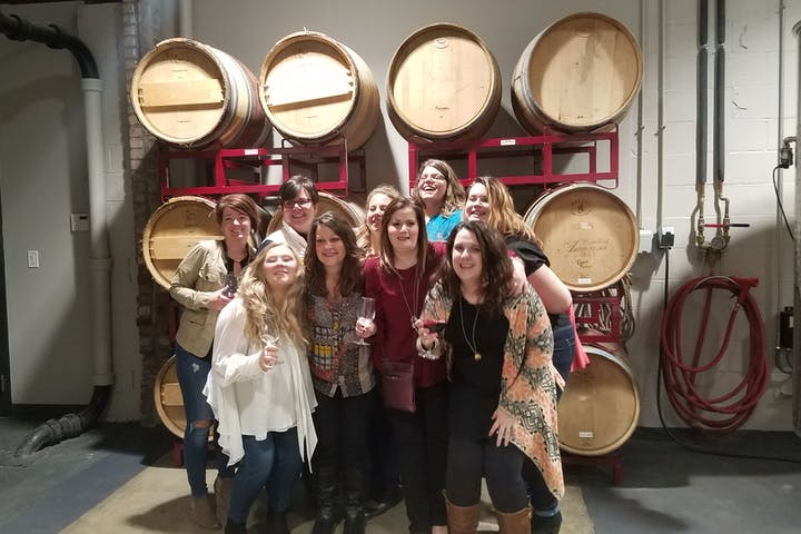 group of friends smiling in front of wine barrels