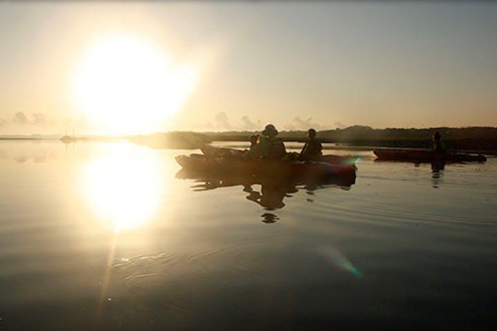 People kayaking during a sunset