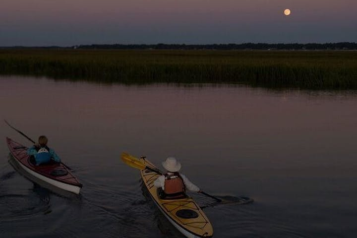 People kayaking during a full moon