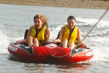 2 teenagers on a tube in the water