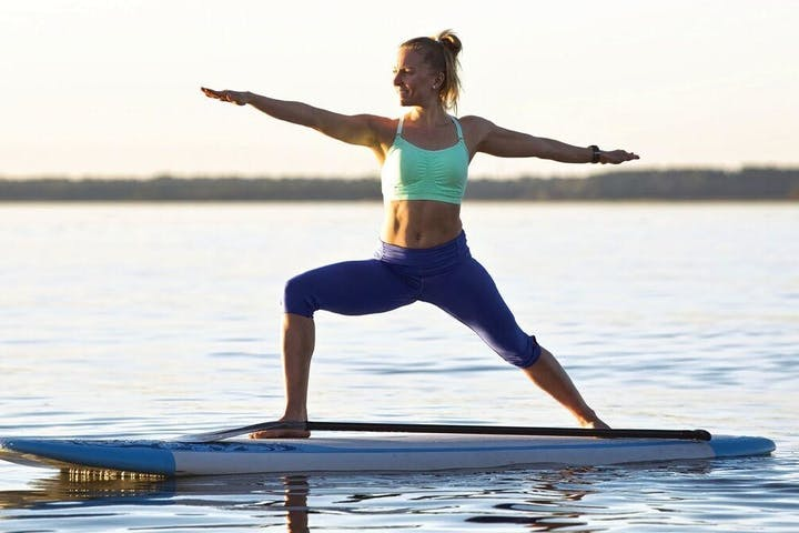 Girl doing yoga on stand up paddle board in the water