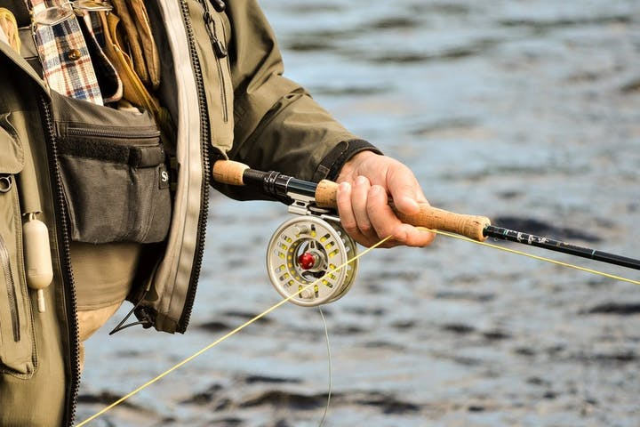Person holding a fly fishing rod & reel near water