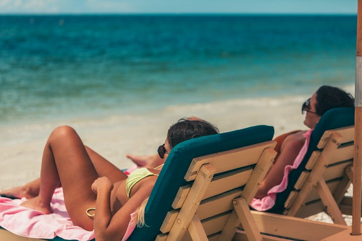 Two girls relaxing under an umbrella on beach chairs