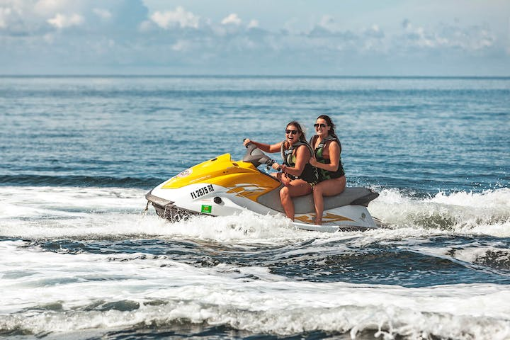 Two girls laughing and smiling while jet skiing