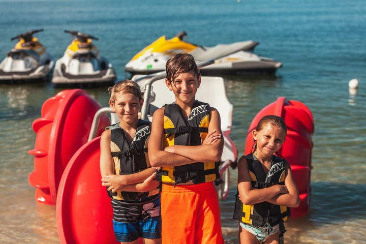 3 kids standing in front of a pedal boat with their arms crossed smiling
