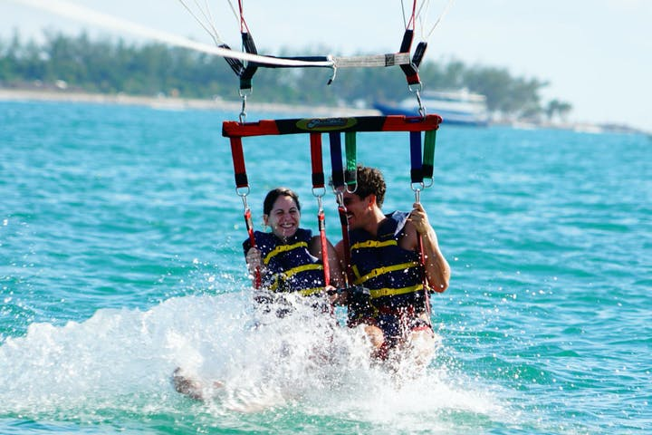 a couple splashing down on a parasail