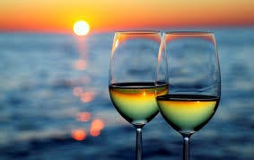wine in glasses with ocean and sunset