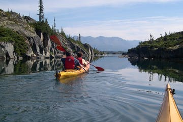 View of kayakers paddling ahead