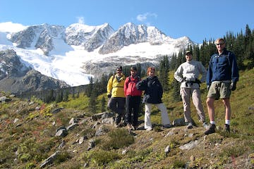 Group of hikers standing for picture in grassy clearing in the mountains