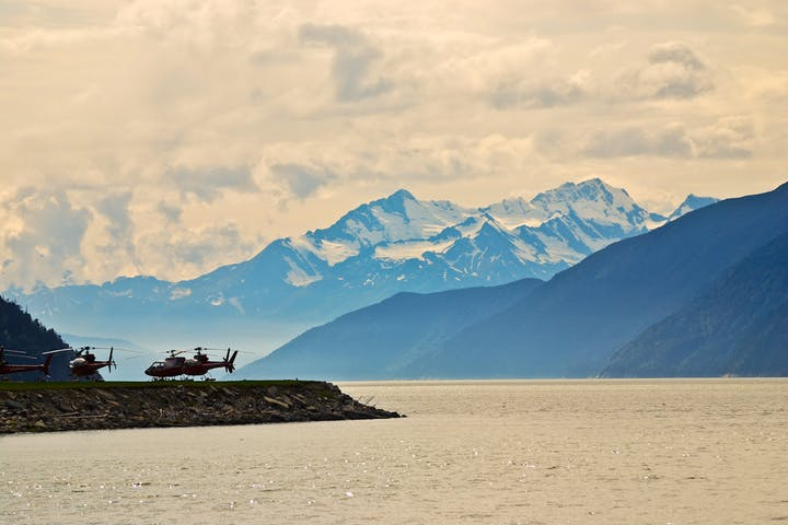 Helicopter landing on landing pad near lake in Alaska