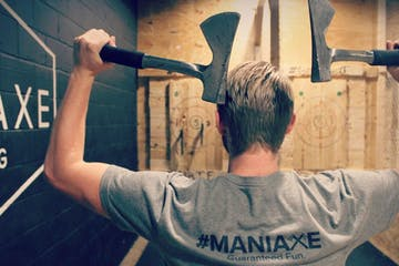 man throwing two axes