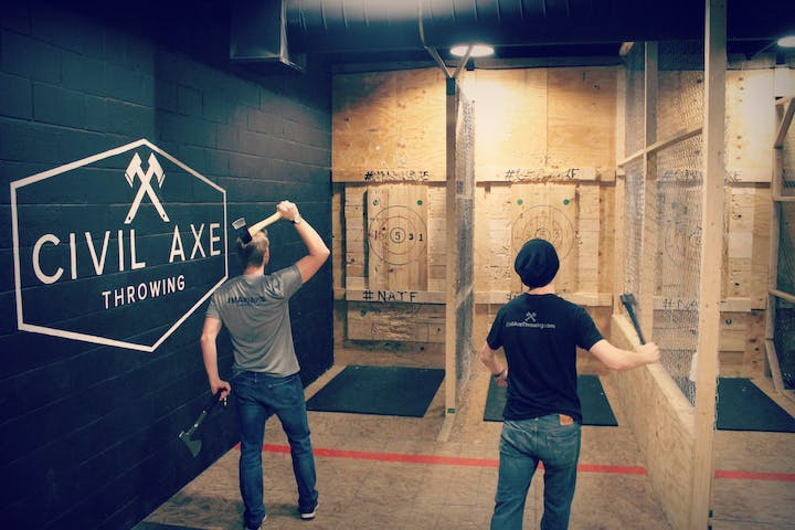 two men throwing axes