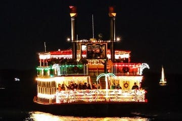 riverboat with christmas lights at night on the water