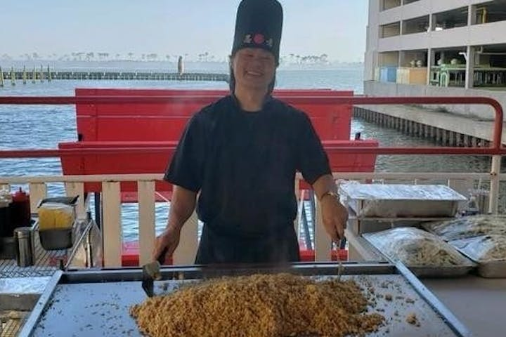 Hibachi chef making food on dinner cruise smiling