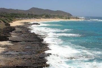 Waves crashing against beach in Oahu