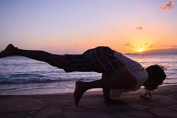 Jonathon doing a yoga pose on the beach at sunset
