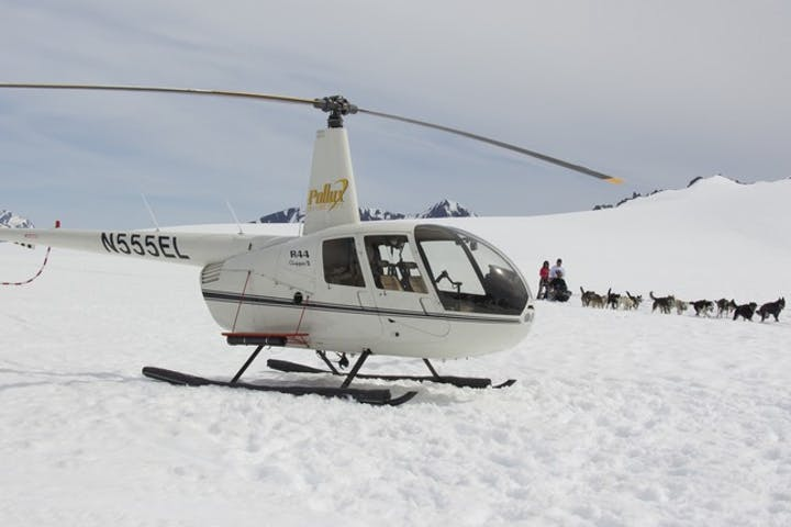 Helicopter landed on a glacier with sled dogs in the background