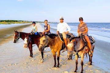 Four horseback riders on the beach