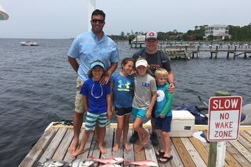 Group of kids standing with adult with fish at their feet on pier