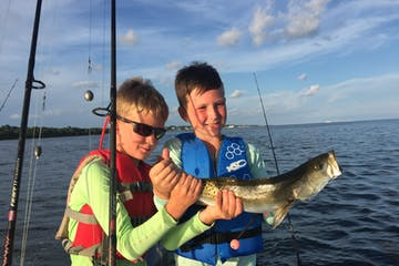 Two young boys holding fish up on the boat
