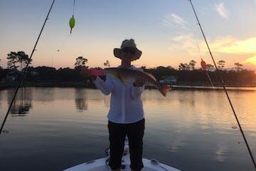 Woman fishing during sunset