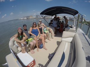 A group of friends posing for a photo while relaxing in their pontoon boat