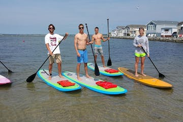 A group of men posing for a photo while on their stand up paddleboards
