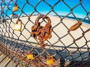 very rusty lock on a fence looking over the beach in Ocean City