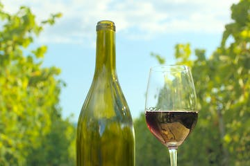 Glass of wine with wine bottle in front of vineyards on the background. Green bottle and glass of wine on the canvas cloth. Alcohol and food composition for restaurant menu.