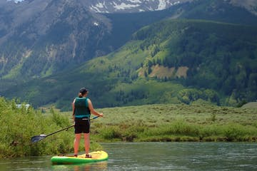 Woman paddle boarding with mountains in the background