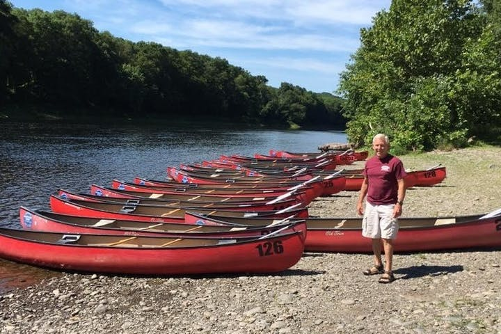 Man next to canoes on beach
