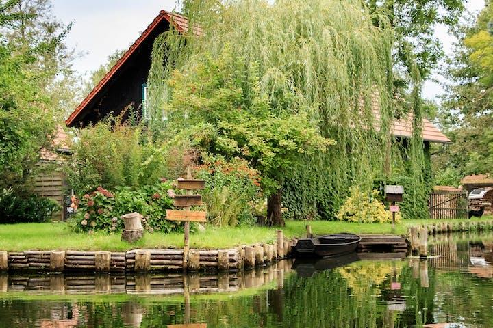 Foto von einem traditionellem Haus an einem Fluss im Spreewald