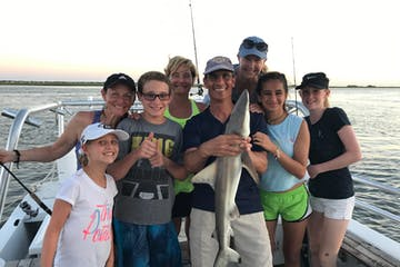 Family holding up small shark caught on fishing trip