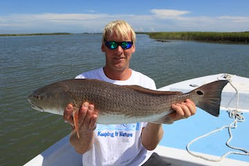 Man holding up large redfish on his boat
