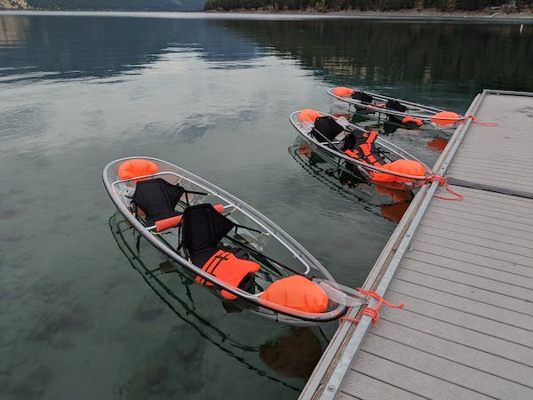 Clear glass kayaks on water dock
