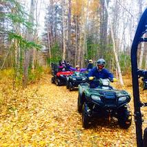 A group ATVs through beautiful Autumn woods in Alaska