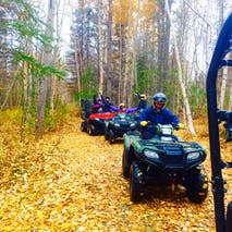 A group ATVs through beautiful Autumn woods in Alaska