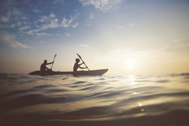 2 people kayaking during a sunset