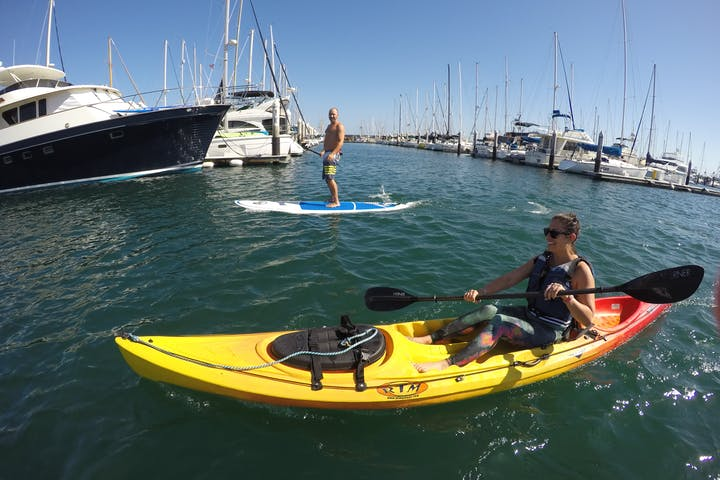 Kayaker and stand up paddle boarder in the water near the marina
