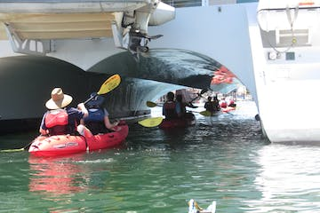 People kayaking underneath an opening of a ship